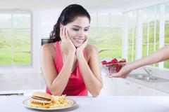 Woman Having Choice Between Fast Food and Strawberry - stock photo