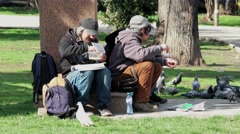 Group homeless vagabonds city park eating free food arms Stock Footage
