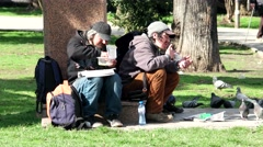 Group homeless bums eat the street food from the hands of volunteers Stock Footage