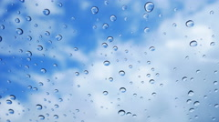 Water splash dripping on glass with blue sky background - stock footage