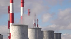 Smoke stacks and cooling towers against cloudy sky Stock Footage