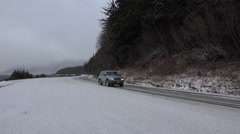 Snowy Road on Coast with SUV Passing in Winter slow pan 4K Stock Footage