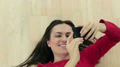 Top view of beautiful girl making selfie while lying on the floor, time lapse HD Stock Footage