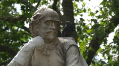 Bird relaxing on William Shakespeare statue in London - stock footage