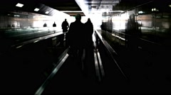 The dark shapes of people moving in an underground tunnel to the light. Stock Footage