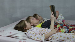 Mom reading the book to son and daughter bedtime - stock footage