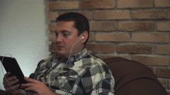 Man in earphone talking through tablet Stock Footage