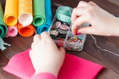 Female hand with needlework objects on wood table - stock photo
