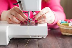 Close-up of hands working on a sewing machine Stock Photos