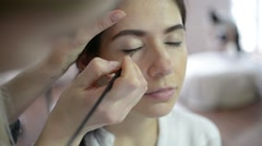 makeup artist working with a beautiful brunette model - eyeliner and lips - stock footage