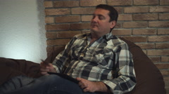 A man sitting in a chair makes a purchase on your tablet Stock Footage