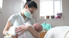 Mother in the respiratory mask holding sleepy newborn baby girl in hands - stock footage