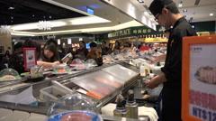 Japanese restaurant, open kitchen, chef prepares sushi, conveyor belt, Asia Stock Footage