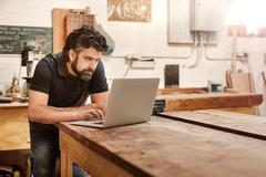 Small business owner in his workshop studio with laptop - stock photo