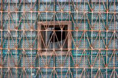 glass block of the old window covered with rusty grid for construction design - stock photo
