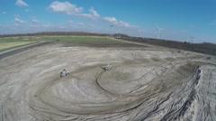 Aerial motocross dirt track motorcross rider moving behind construction 4k Stock Footage