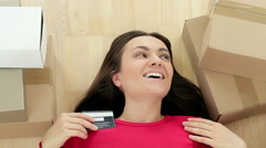 High angle view of a happy young woman with credit card lying on the floor HD Stock Footage