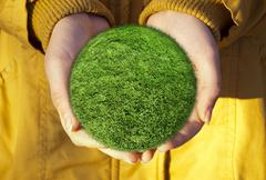 Green grass globe in hands - stock photo