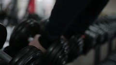 Hands of strong male athlete taking heavy dumbbells during workout in the gym Stock Footage