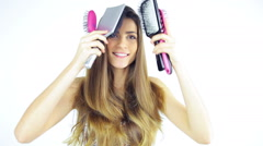 Beautiful young woman brushing long silky hair with many brushes looking camera Stock Footage