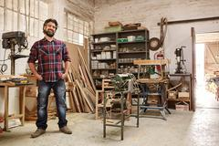 Craftsman in his workshop with heavy-duty woodwork machinery Stock Photos