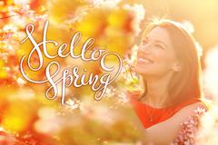 Stock Photo of young woman enjoying smell in a flowering spring garden with letters Hello