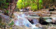 Waterfall flow through wet stones and rock cascades in beautiful tropical forest Stock Footage