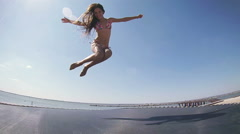 Girl jumping on trampoline Stock Footage