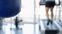Defocused man walking on treadmill, punching bag hanging in gym, background shot - stock footage