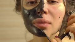 Beautiful woman removing elastic black face pack from her face - stock footage