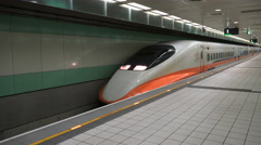 A high speed bullet train leaves the platform of a railway station in Taiwan Stock Footage