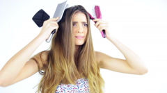 Beautiful young woman unhappy about long messy hair brushing with many brushes Stock Footage