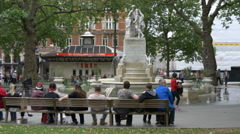 Tourists relaxing in front of William Shakespeare statue in London - stock footage