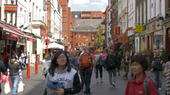 Multi-ethnic tourists walking on Gerrard Street in London Stock Footage