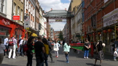 People walking by the Chinatown archway in London Stock Footage