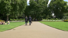 Men walking and others relaxing in a park in London Stock Footage