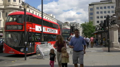 Red buses and cars driving in front of the Charing Cross station, London Stock Footage