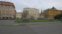 Cars driving, people walking and sitting on bench on Marsala Tita street, Zagreb Stock Footage