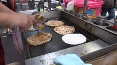 A street vendor prepares pancakes in a popular shopping district in Taipei - stock footage