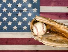 Close up of baseball mitt and ball with painted boards of USA flag. Stock Photos