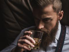 Cheerful bearded businessman is drinking expensive whisky Stock Photos
