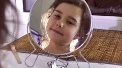 Stock Video Footage of teen girl combing her hair before a mirror indoor