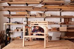 Artisan manufacturing a wooden chair frame in his studio Stock Photos