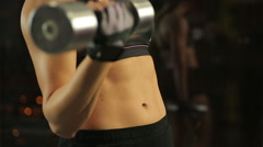 Strong female athlete doing dumbbell curls, preparing for sports competition - stock footage