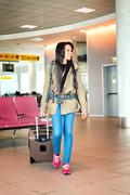 Hispanic treveling young walking with suicase in airport terminal gate Kuvituskuvat