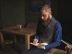 Cheerful bearded author is writing a poem - stock photo