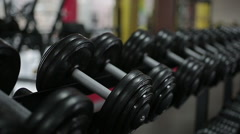 Atmosphere in the gym, male athlete using fixed-weight dumbbells during workout Stock Footage