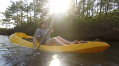 Girl riding canoe in the river. Having fun outdoors as paddling a small canoe   Stock Footage