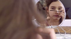 Teen girl paints eyelashes before mirror Stock Footage