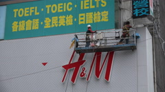 Asian construction workers painting, Western retail clothing store, Taipei Stock Footage